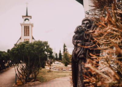 Rzeźba na tle Kościoła Matki Bożej Nieustającej Pomocy w Skorzewie